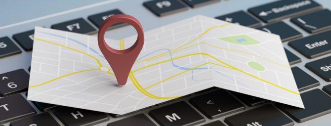 Arte com mapa e pin de sinalização em cima de um teclado de computador